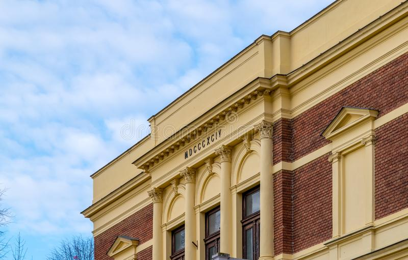 An old building with yellow tones, with roman numbers representing the year it was built in Sibiu, Romania.  stock photos