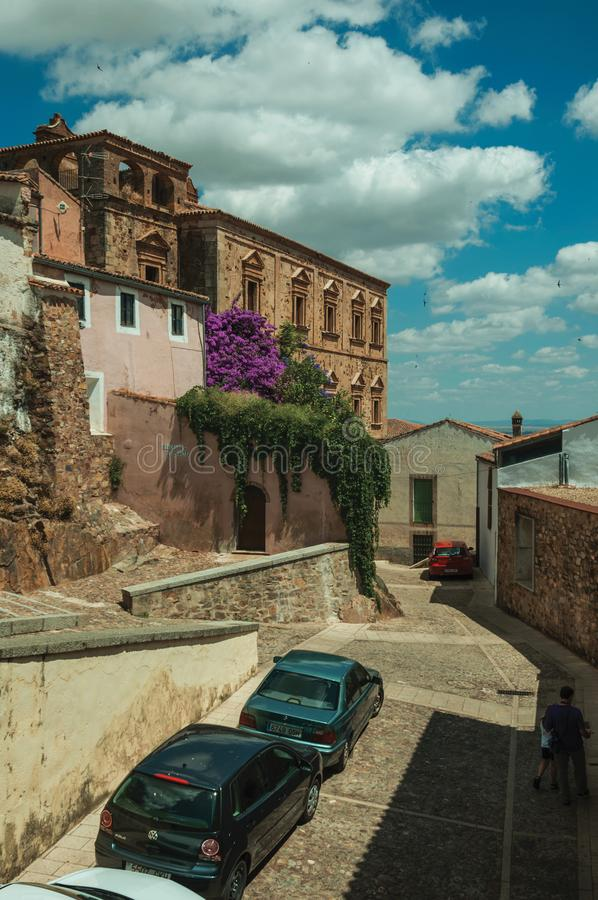 Old buildings and flowering trees over an alleyway with cars at Caceres stock images