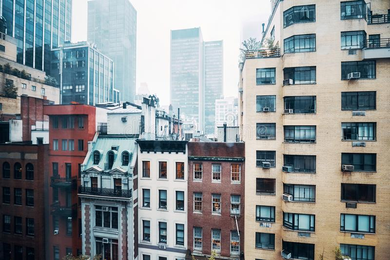 Old buildings in Midtown Manhattan, NYC. Vintage toned picture of old apartment buildings in Midtown Manhattan on a rainy day, New York, USA stock photography