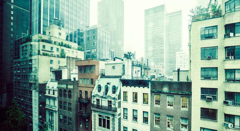 Old buildings in Midtown Manhattan, NYC. Vintage toned picture of old apartment buildings in Midtown Manhattan on a rainy day, New York, USA stock images
