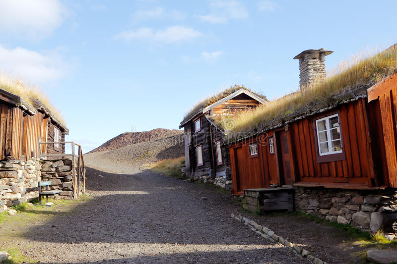 Old buildings in Roros. Old wooden buildings with thatched roofs adjacent to the heap in the mining town of Roros in Norway royalty free stock photo