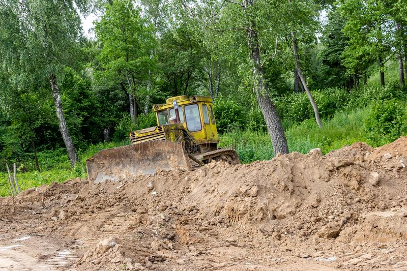 Old bulldozer spreads land. Near the forest stock photography