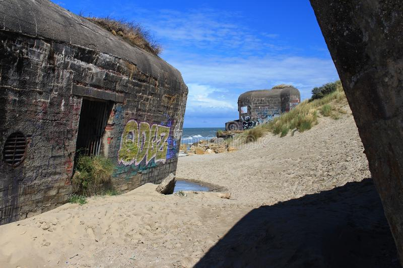 Old bunkers in sand at coast. Old abandoned bunkers in sand at coast look like a forgotten toys on playground. History of these bunkers fades away in sand royalty free stock photos