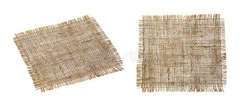 Old burlap fabric napkin isolated on white background. Old burlap fabric napkin closeup. Rough linen jute, sackcloth piece isolated on white background with stock photos