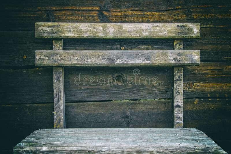 Old burned boards with nails in brown and black colour as a background. a wooden chair stands before that stock photo