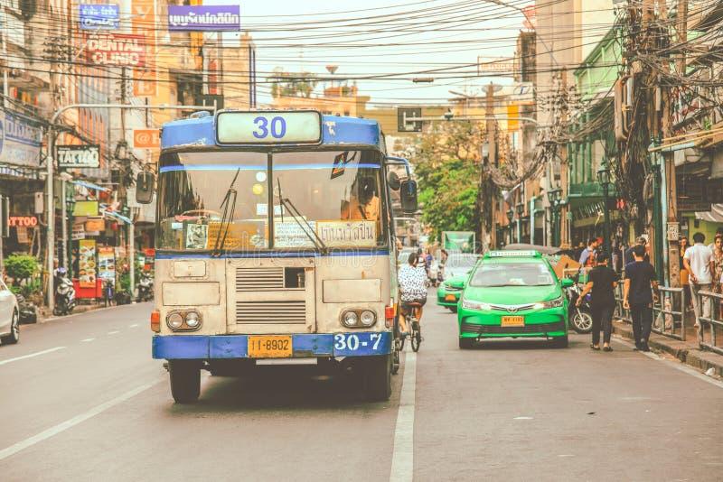 Old bus drives through Bangkok city centre stock images