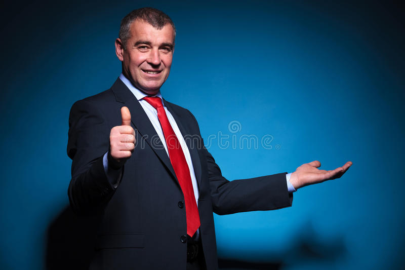 Old business man presenting and making ok stock photography