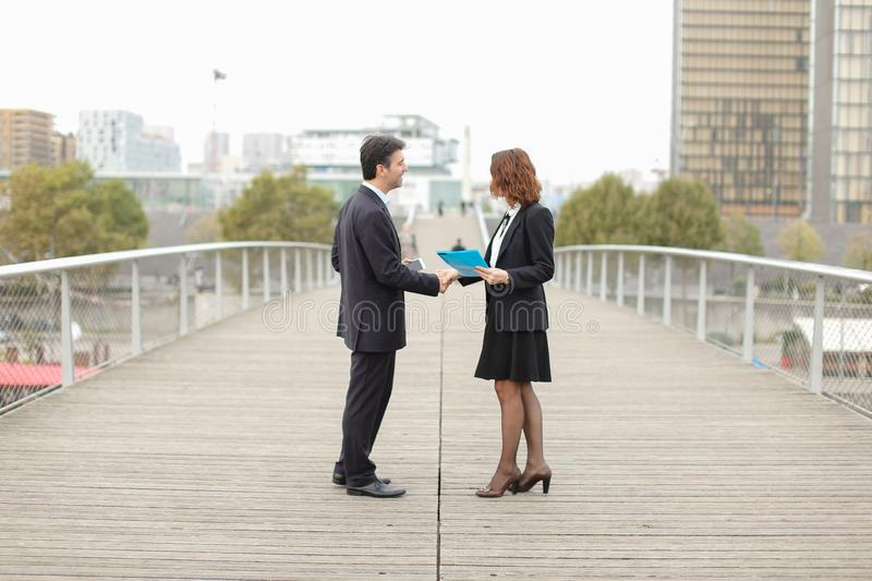 old IT business partners man with smartphone and woman meet stock image