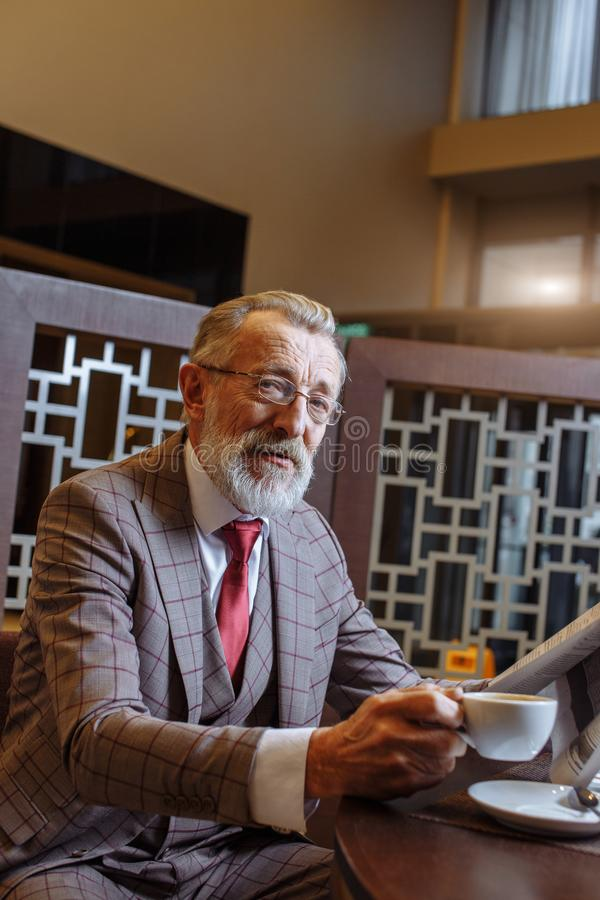 Old Businessman with laptop at coffee break in his office concept stock photo