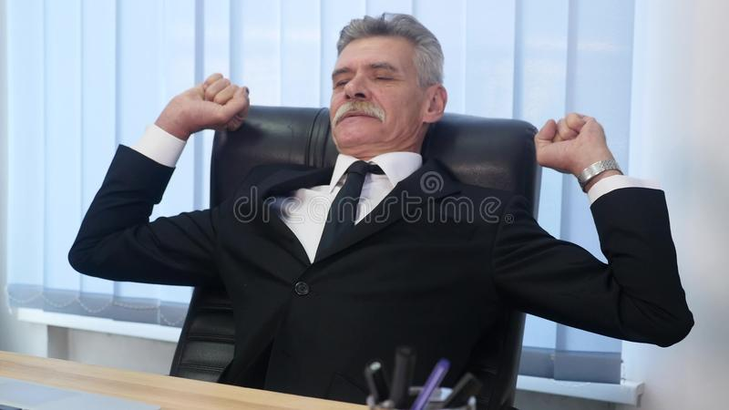 Old businessman leaned back in his office chair, he smile and daydreaming royalty free stock photo