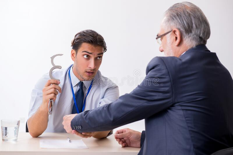 Old businessman meeting with advocate in pre-trial detention. Old businessman meeting with advocate in pretrial detention royalty free stock photography