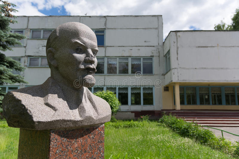 Old bust of Lenin on the background of the old Soviet building stock photo