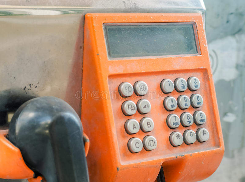 Old button number on orange public telephone royalty free stock photography