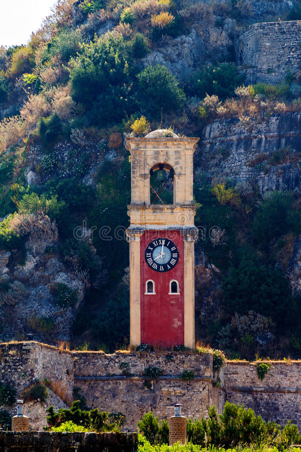 Old Byzantine clock tower on green mountains stock photos