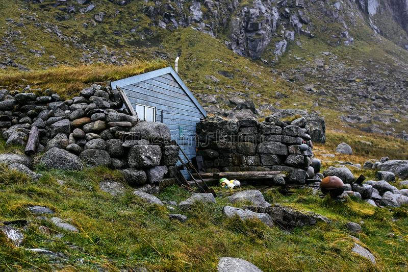 Remote blue wooden cabin Stokkvika Hytta at the coast of Lofoten Islands in Norway surrounded by stones, grass and mountains. stock photography