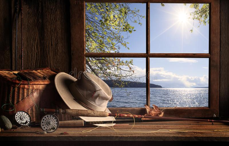 Old Cabin Window with View of Puget Sound. An old cabin wood table with fly fishing equipment including wicker fishing creel, rods and reels, hat and hand tied royalty free stock photo