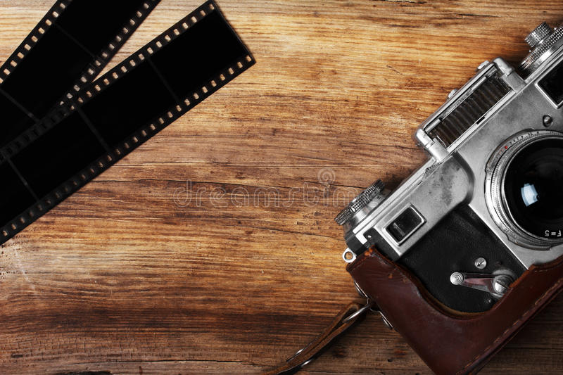 Old camera and blank film strip. On wooden table royalty free stock images