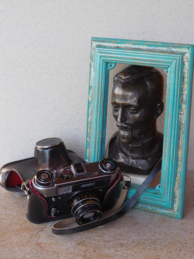 Old camera Fed with a bronze statue of Felix Edmundovich Dzerzhinsky in a wooden photo frame. stock photos