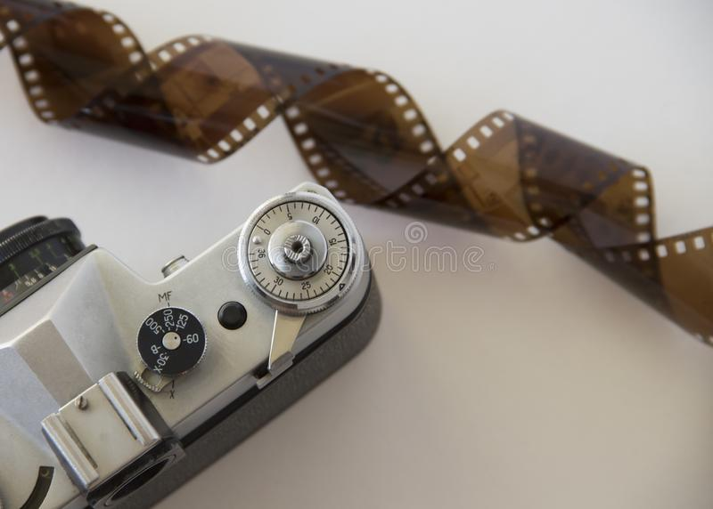 Old camera and film on white background. Analog photography: a camera with a lens and film inside on a white background stock images