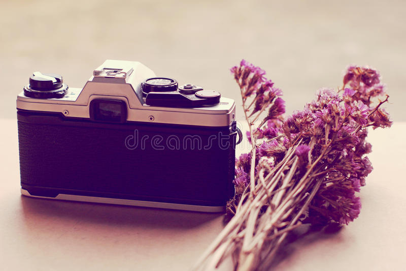 Old camera and flowers with retro filter effect. Old camera and bunch of flowers with retro filter effect royalty free stock images
