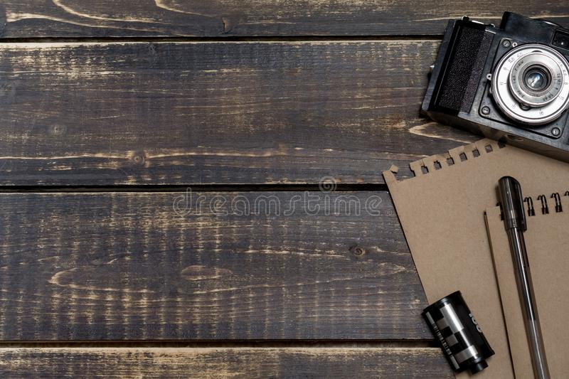 Old camera, a notepad for notes and a film on a dark wooden back royalty free stock photography