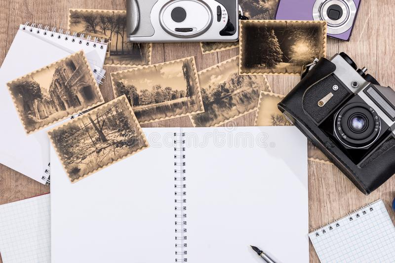 Old camera with pictures and blank notepad royalty free stock photography