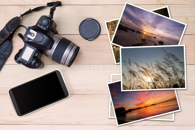 Old camera, smartphone and stack of photos on wooden background. Camera technology or photography hobby stock photos