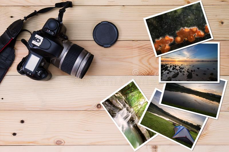 Old camera and stack of photos on vintage grunge wooden background. Photography hobby lifestyle concept stock image
