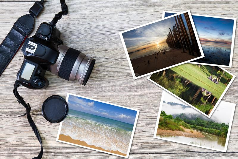 Old camera and stack of photos on vintage grunge wooden background. Photography hobby lifestyle concept stock photo
