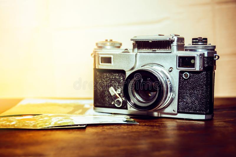 Old camera is on the table on a stack of photos.  royalty free stock photography