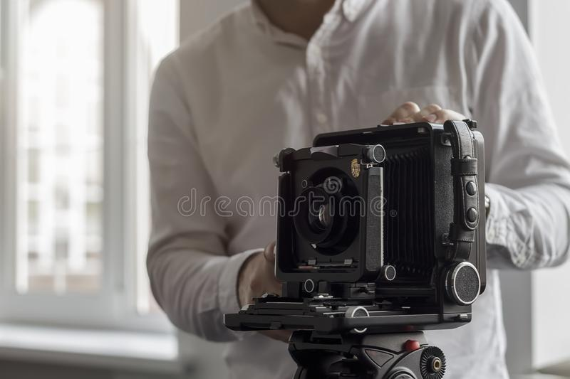 The old camera on a tripod stands on a background of a wall stock images