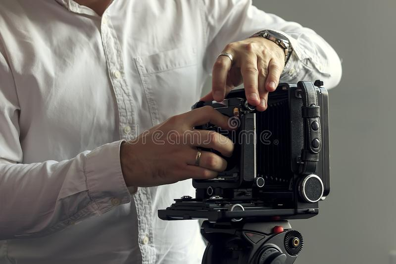 The old camera on a tripod stands on a background of a wall stock photo