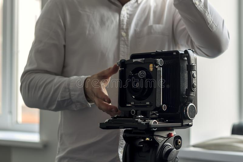 The old camera on a tripod stands on a background of a wall royalty free stock images