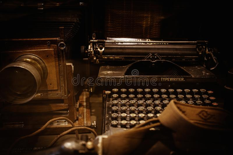 Old camera and typewriter. On a table stock photo