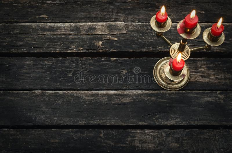 Old candle in the candle holder. Old candlestick with four burning candles on an empty wooden table background with copy space stock photos