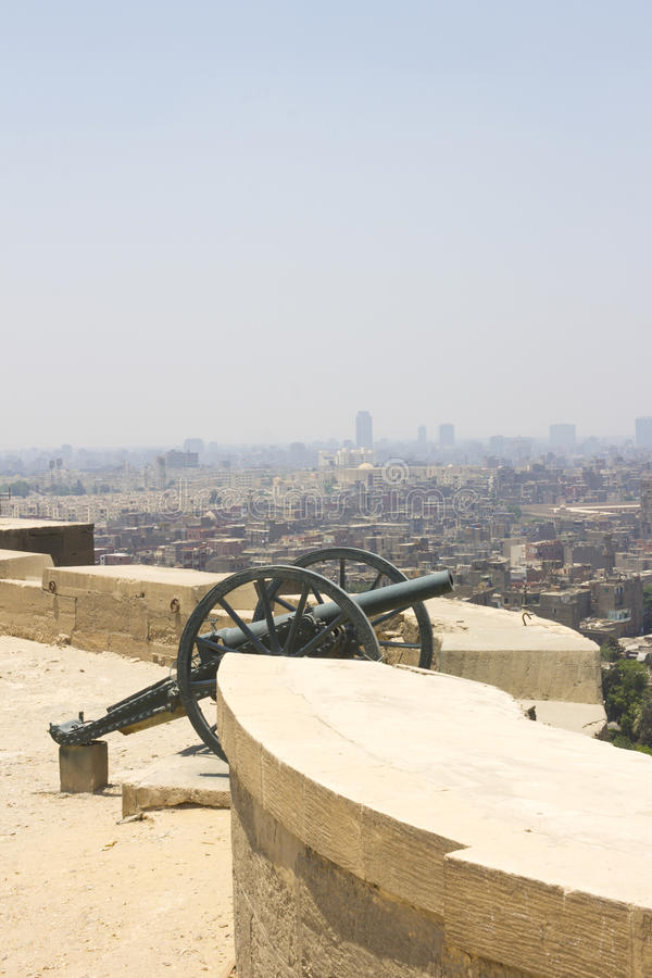 Old Cannon with Cairo city in the bakcground. Old Cannon located in front of the Cairo citadel which used to have an important function during ramadan with Cairo royalty free stock images