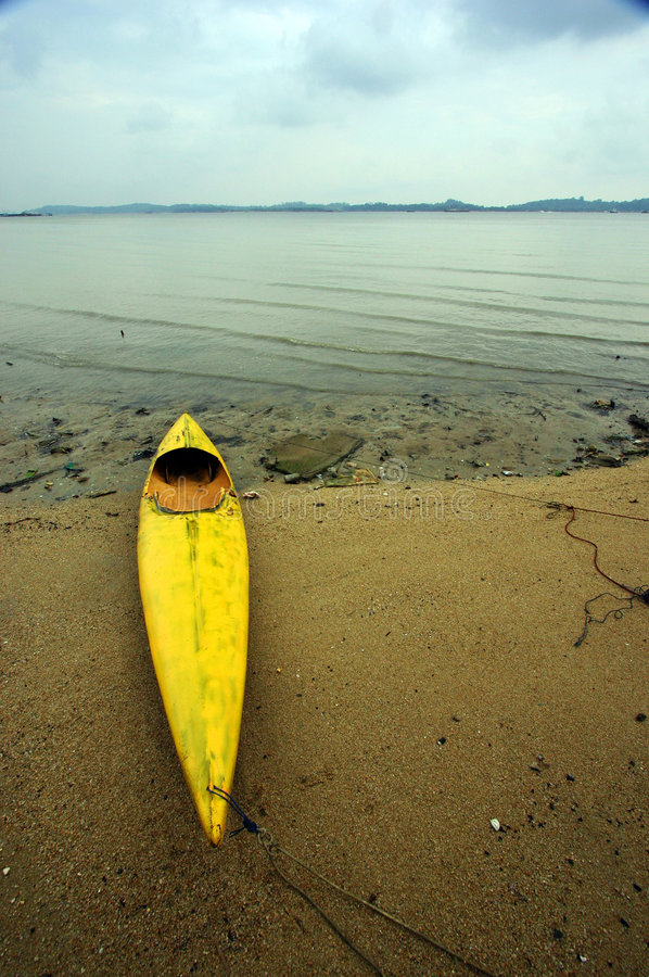 Old canoe on mudflat beach. An old dilapidated canoe boat lies forlornly on sandy beach with mudflat behind. Calm and tranquil outdoor nature scene with a sad stock photography