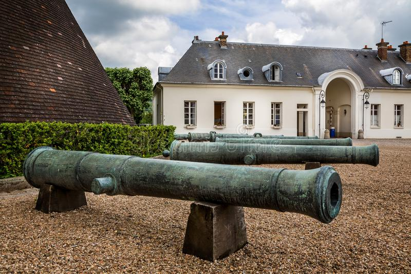 Old canons in front of large former conical glass making kiln in Chateau Verrerie, Le Creusot, France. On 20 June 2013 stock photos