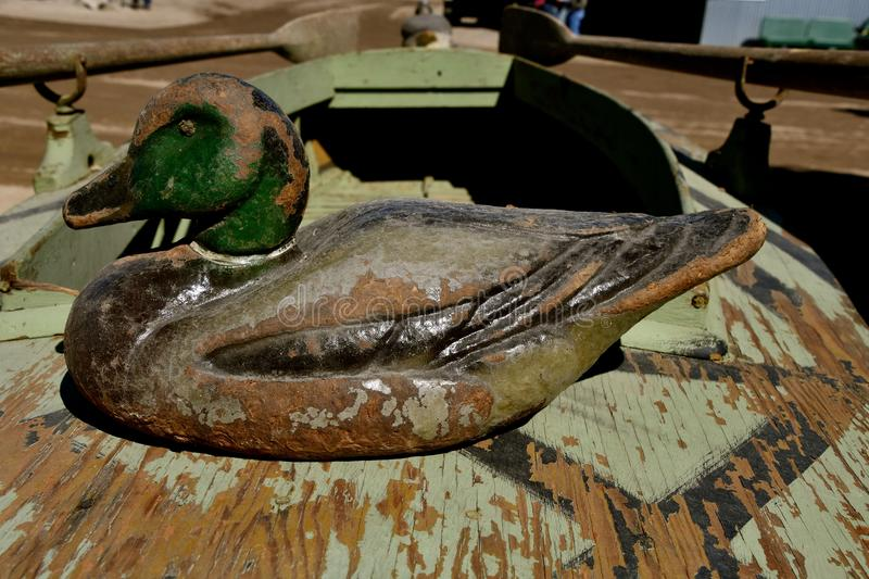Old canvas duck decoys. An old canvas layered duck mallard decoy rests on the seat of a primitive oar propelled duck boat stock photo