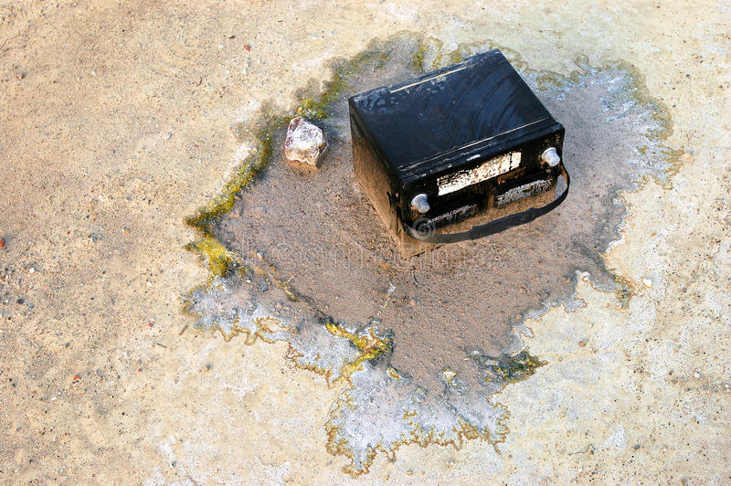 Old Car Battery on the Ground. Old Automotive Battery acidifies the ground around it stock photos