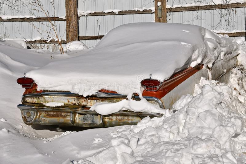Old car buried in a snow bank. An old rusty car is buried in a snowdrift with only blinkers, taillights and bumper exposed stock image