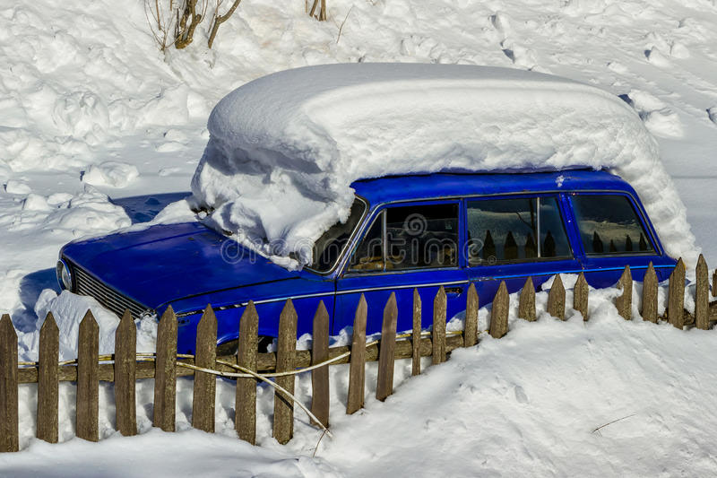 Old car covered with a thick layer of snow. Near the wooden fence royalty free stock photo