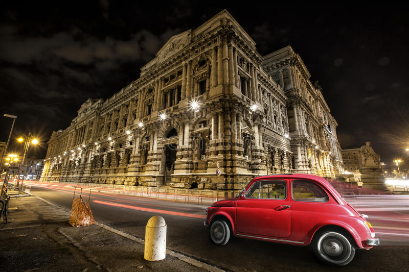 Old car Italian red by night. Italian historic monument. Light trails of car headlights. Palace of Justice, Supreme Court of Cassation and the Judicial Public royalty free stock photos