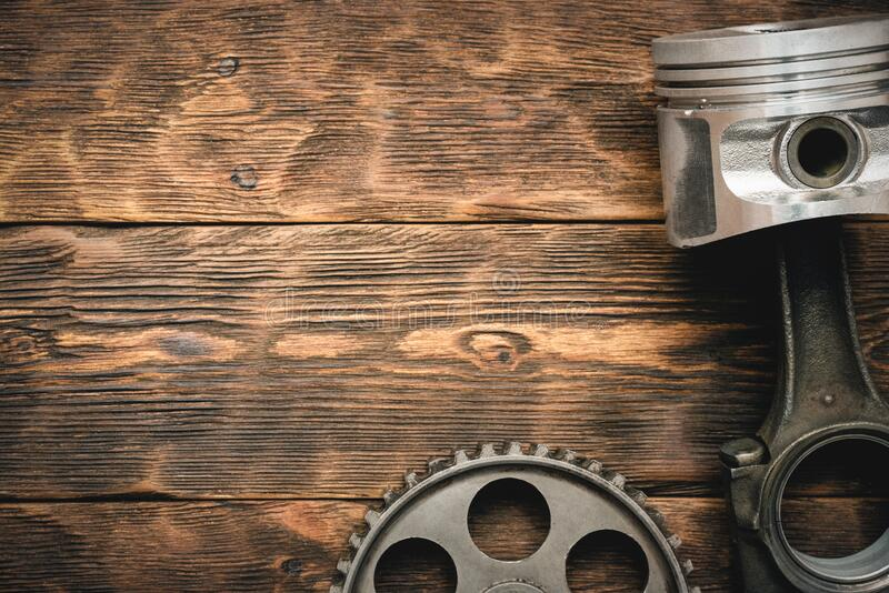 Old car spare parts. On brown wooden workbench background with copy space royalty free stock image