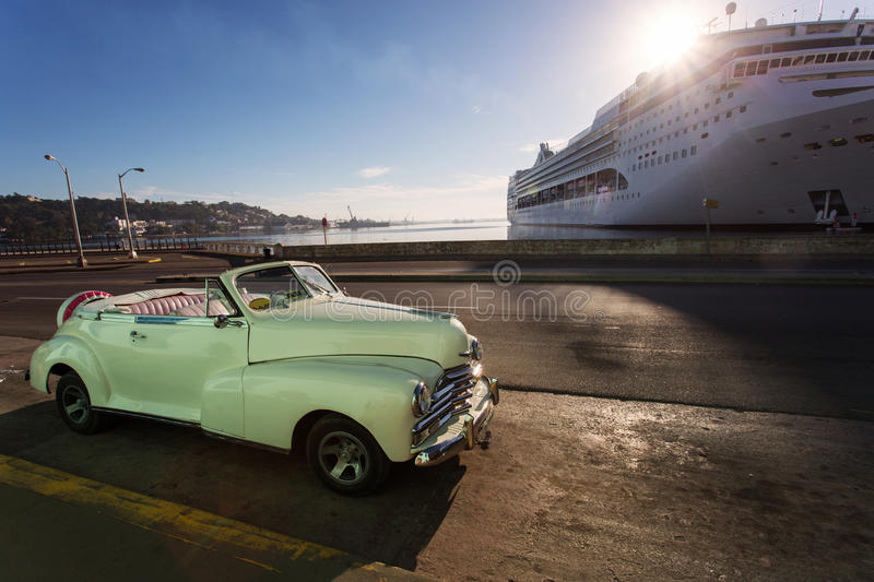 Old car on street of Havana with cruise ship in background at sunrise, Cuba.  stock photography
