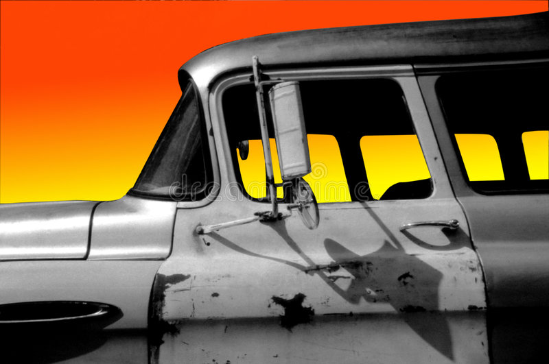 Old Car at Sunset. Black and white image of old rusty car with a gradient sunset background stock photo