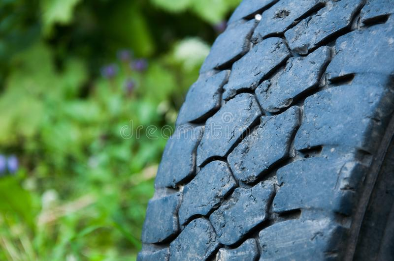 An old car tire buried in the ground. Part of the wheel. royalty free stock photo