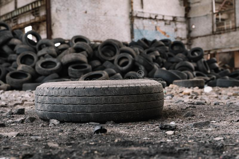 Old car tire lying on the ground of an abandoned factory stock image