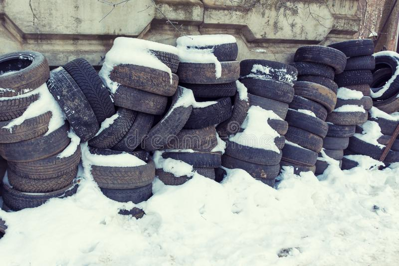 Old car tires covered by snow stock photos