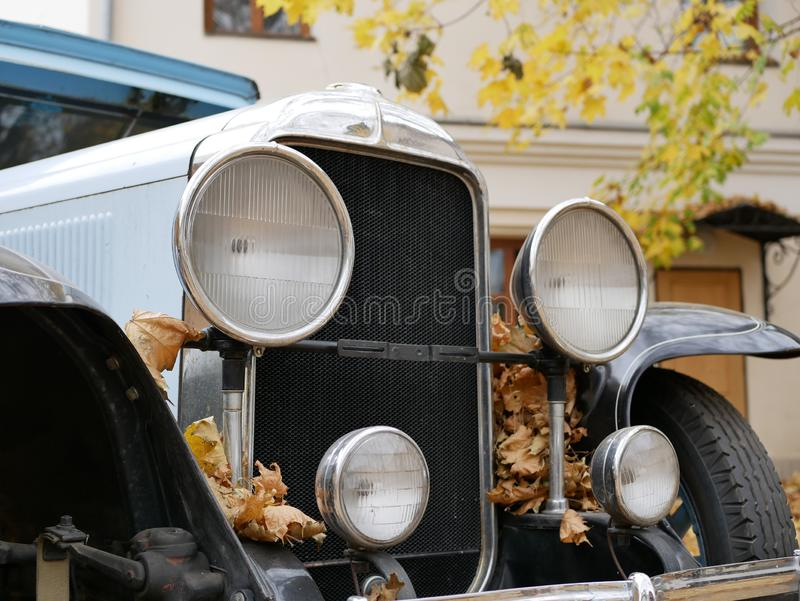 An old car in the yard which is covered with yellow maple leaves. An old car in the yard. an old blue car in the yard which is covered with yellow maple leaves royalty free stock photos